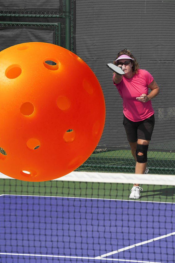 A woman playing pickleball wearing a pink t-shirt and pink visor.