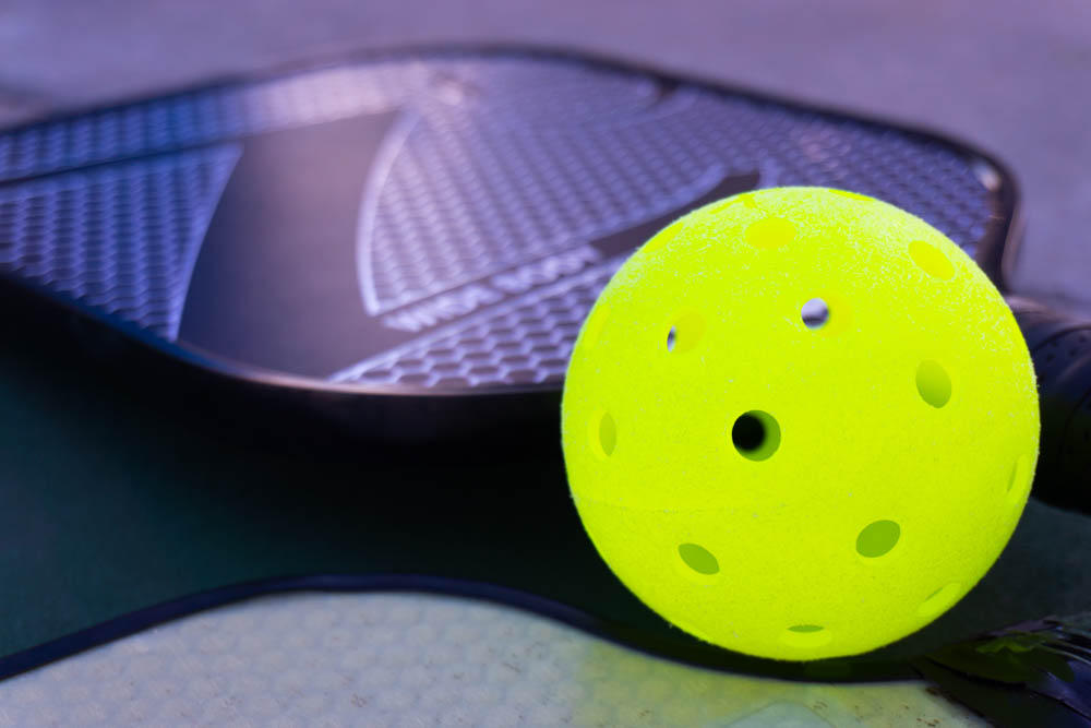 Pickleball paddle and ball on court