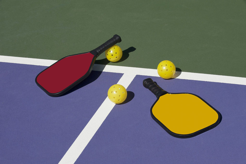A red pickleball paddle and yellow pickleball paddle with three yellow pickleball balls on a court