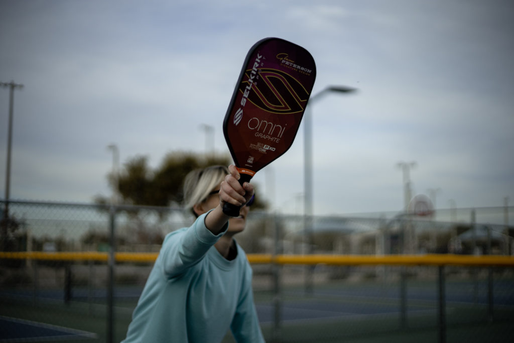 Woman hitting pickleball paddle during a game
