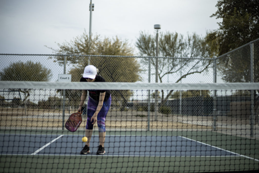A solo pickleball player on an empty pickleball court